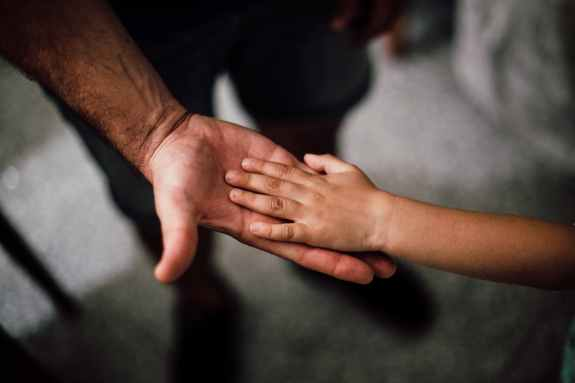 selective focus photography of child s hand on person s palm